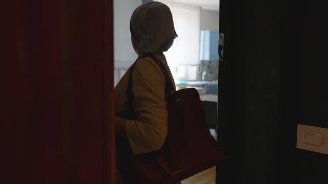 vidéos et rushes de jeune femme allant de la maison navettant au travail - vêtement religieux