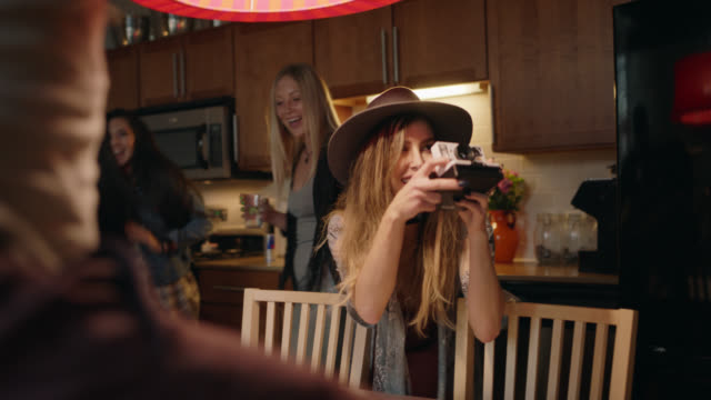 young woman grabs instant camera and snaps a picture as friends dance around the kitchen table at wild house party. - leisure activity stock videos & royalty-free footage