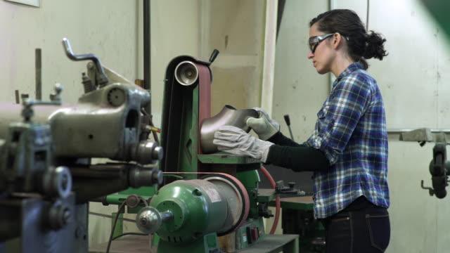 vídeos y material grabado en eventos de stock de young woman grinding a pipe in a factory - camisa a cuadros