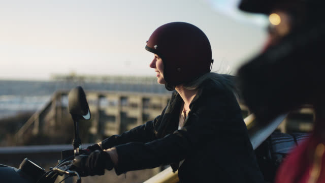 ms slo mo. young woman grips motorcycle handles and looks out over the ocean. - ヘルメット点の映像素材/bロール