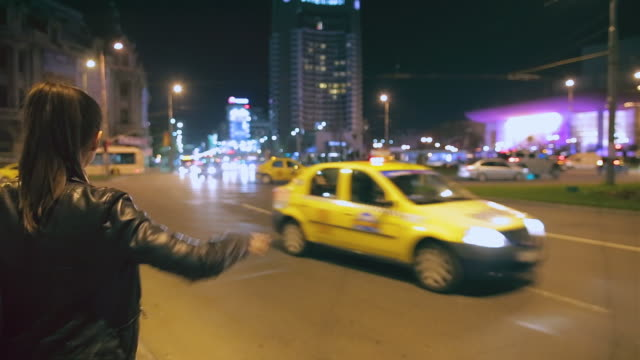 Young woman hails a taxi cab.