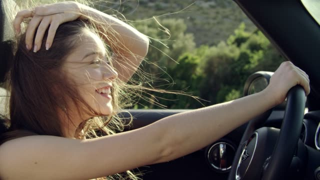 young woman hair blowing in wind while riding in cabrio car - red lipstick stock videos & royalty-free footage