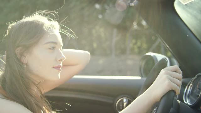 young woman hair blowing in wind while riding in convertible car - red lipstick stock videos & royalty-free footage