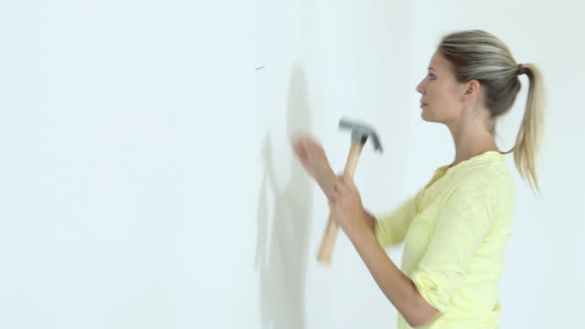 young woman hammering nail into wall and hanging picture - hammer stock videos & royalty-free footage