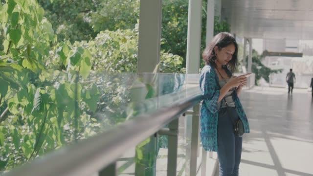 vidéos et rushes de main de jeune femme tenant un téléphone intelligent à l'extérieur dans la ville moderne. - espace texte