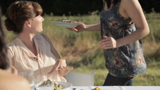 vidéos et rushes de young woman handing food to friends at outdoor dinner party - donner