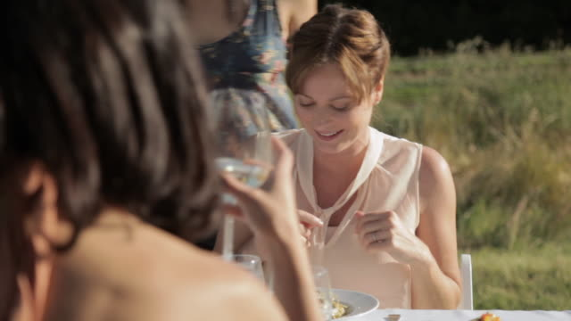 vidéos et rushes de young woman handing meal to people at outdoor dinner party, man eating - assiette