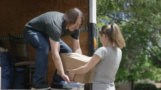 a young woman hands a man in a moving van a box - hair back stock videos & royalty-free footage