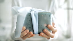 Young woman hands holding gift box