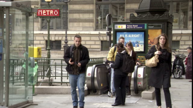 a young woman hands out pamphlets to commuters as they exit a metro station. - brochure stock videos & royalty-free footage