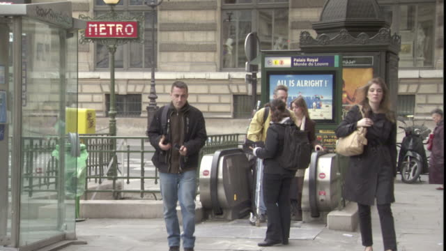 a young woman hands out pamphlets to commuters as they exit a metro station. - brochure stock videos and b-roll footage