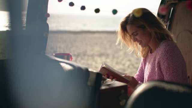 stockvideo's en b-roll-footage met ms young woman hanging out at the beach in her camper van - reading