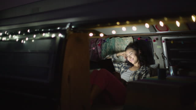 vídeos de stock e filmes b-roll de young woman hanging out in her camper van at night - acampar