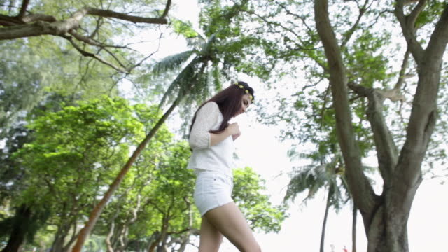 WS Young woman happily walking under the trees.