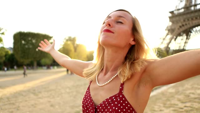 Young woman harms outstretched at the Eiffel Tower at sunset