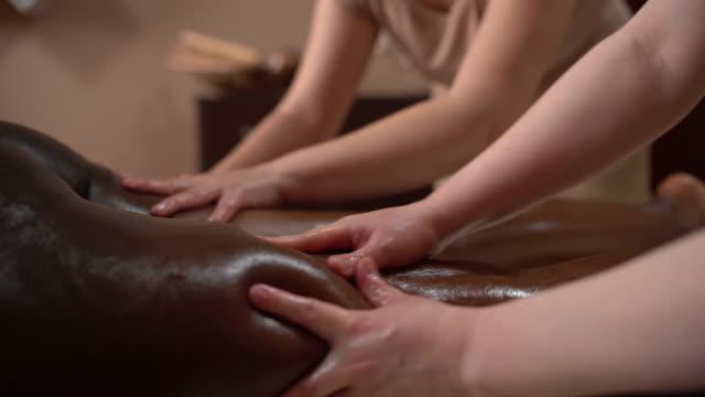 vidéos et rushes de la jeune femme a le massage relaxant de corps - banc de massage