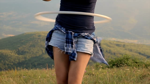 young woman have a fun with hula hoop on the top of the mountain - plastic hoop stock videos & royalty-free footage