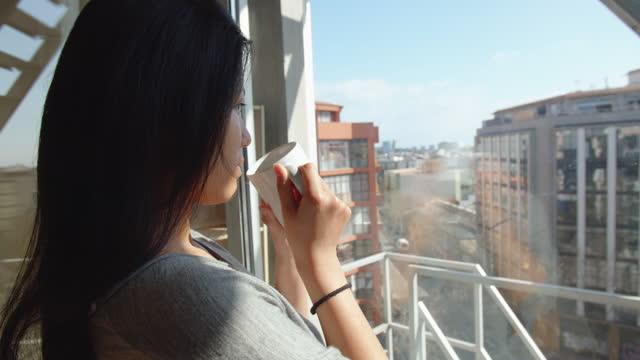 young woman having a cup of coffee or tea at office contemplating industrial buildings, poblenou district, barcelona - fönsterrad bildbanksvideor och videomaterial från bakom kulisserna