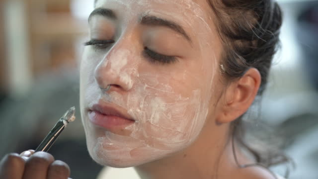 a young woman having a face mask applied. - beautician stock videos & royalty-free footage
