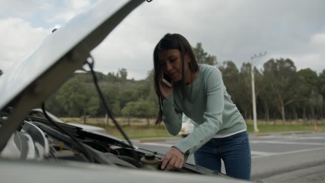 vidéos et rushes de jeune femme ayant la difficulté de voiture appelant à l'assistance de côté de route - capot de voiture