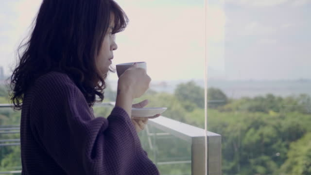 young woman having coffee at home - sunny stock videos & royalty-free footage