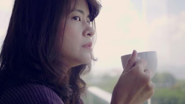 家でコーヒーを飲む若い女性 - 窓越し点の映像素材/bロール