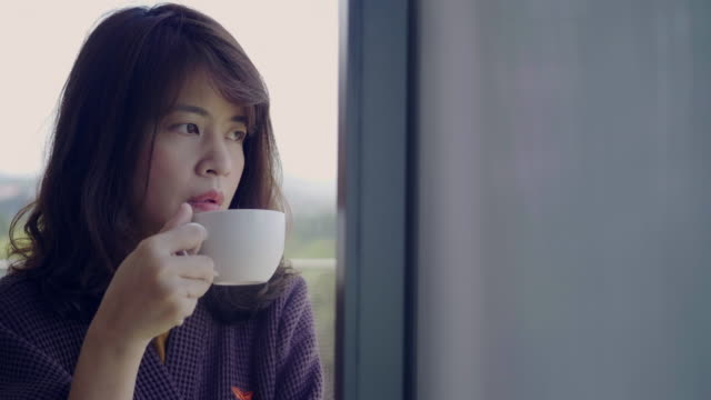 young woman having coffee at home - looking through window stock videos & royalty-free footage