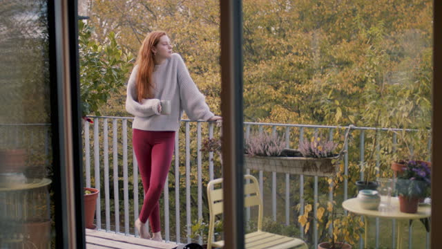 young woman having coffee on balcony at home alone - barefoot stock videos & royalty-free footage