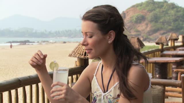 stockvideo's en b-roll-footage met young woman having drink at beach bar - zonnejurk