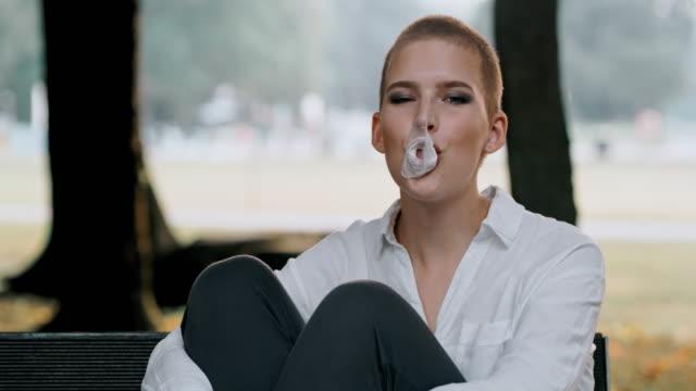 vídeos de stock e filmes b-roll de ds ms young woman having fun chewing a bubble gum in the park - cabelo curto comprimento de cabelo