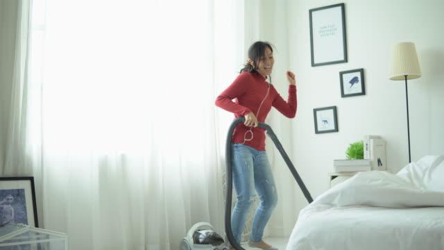 vídeos de stock, filmes e b-roll de mulher nova que tem a casa de limpeza do divertimento com aspirador de p30 - pairando