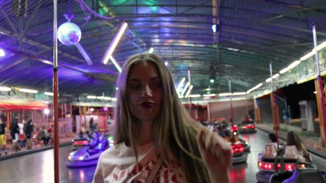 stockvideo's en b-roll-footage met jonge vrouw met plezier in pretpark en rijden bumper cars - botsauto