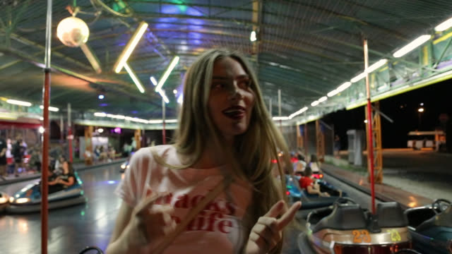 young woman having fun in amusement park and driving bumper cars - bumper car stock videos & royalty-free footage