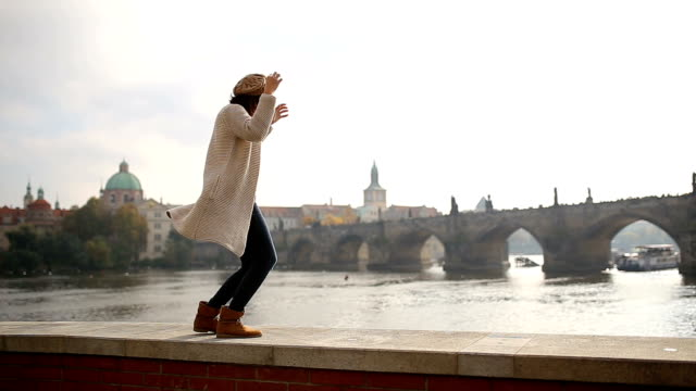 Young woman having fun in Prague,by Charles bridge