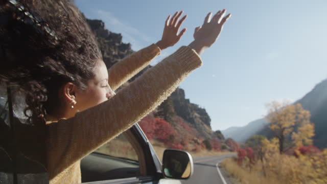 vidéos et rushes de sm young woman having fun on a road trip in the mountains - cheveux bruns