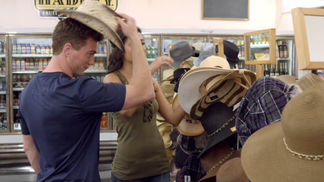 vídeos de stock, filmes e b-roll de ms young woman having fun putting on different hats while shopping in general store and showing off to her boyfriend / cabazon, california, usa - choice