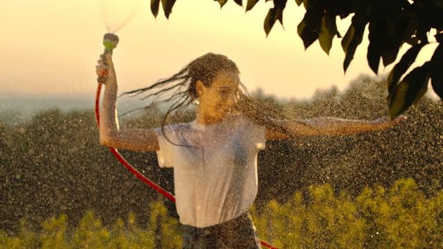 スーパースローmo若い女性は、庭のホースから水で自分自身をスプレー楽しんで - 水撒き点の映像素材/bロール