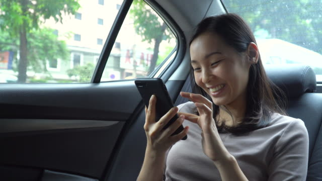 young woman having fun to using mobile phone in car - only young women stock videos & royalty-free footage