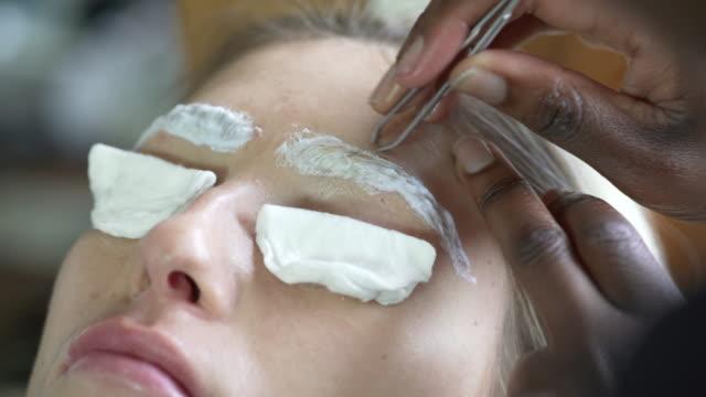 vídeos de stock e filmes b-roll de a young woman having her eyebrows bleached - depilação