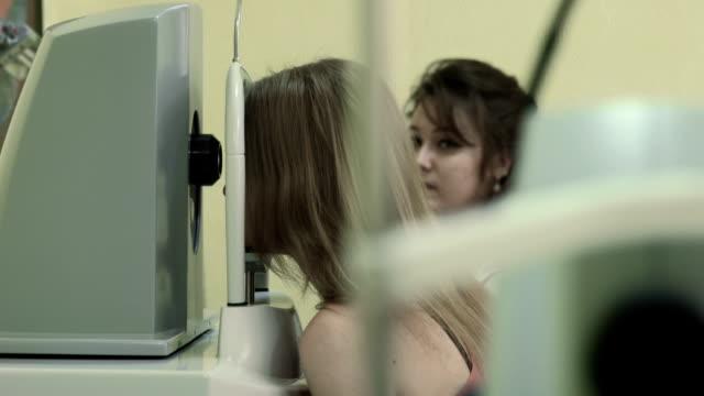 junge frau, die ihr sehkraft geprüft.  eye scanner - optisches gerät stock-videos und b-roll-filmmaterial