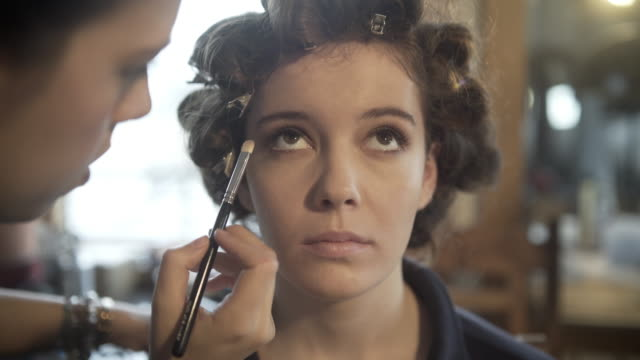 A young woman having her hair and make-up created by a professional make-up artist and hair stylist.