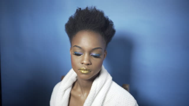 a young woman having her hair and make-up created with gold lipstick and blue glittery eyeshadow. - natural black hair stock videos & royalty-free footage
