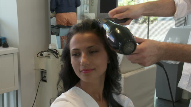 ms young woman having her hair done at hair salon, rome, italy - blow drying hair stock videos and b-roll footage