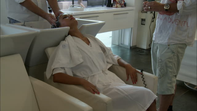 ms young woman having her hair shampooed and massaged at hair salon, rome, italy - kopf nach hinten stock-videos und b-roll-filmmaterial