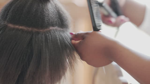a young woman having her hair straightened. in preparation for hair braids - braided hair stock videos & royalty-free footage
