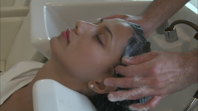 cu young woman having her hair washed at hair salon, rome, italy - kopf nach hinten stock-videos und b-roll-filmmaterial