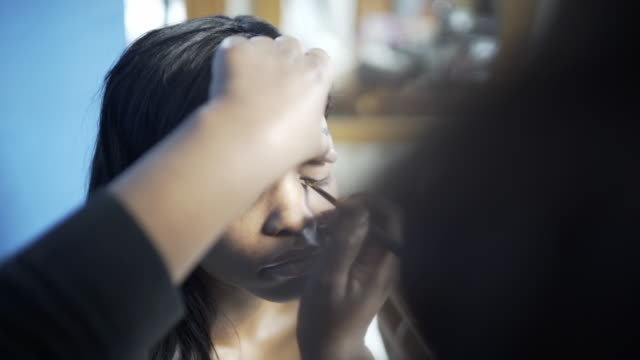 A young woman having her make-up created by a make-up artist applying eyeliner.