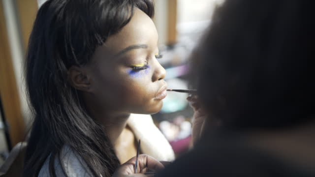 A young woman having her make-up created by a make-up artist applying lipstick.