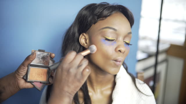 vidéos et rushes de a young woman having her make-up created by a make-up artist contouring her skin. - fard à joues
