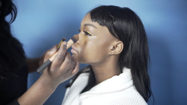 a young woman having her make-up created by a make-up artist. - fard video stock e b–roll